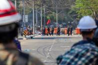 Police are seen in front of a protester barricade during a protest against the military coup in Yangon