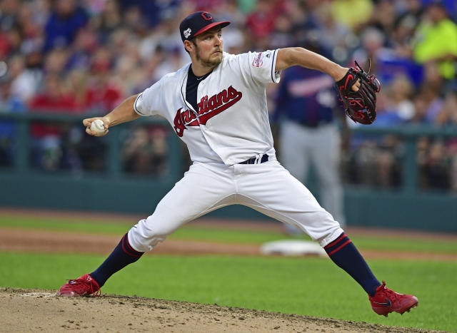 FILE - In this July 13, 2019, file photo, Cleveland Indians starting pitcher Trevor Bauer delivers in the sixth inning of a baseball game against the Minnesota Twins, in Cleveland. The Indians bulked up for the playoff race by trading temperamental starter Trevor Bauer before the deadline to Cincinnati in a three-team deal they hope can help them run down the Minnesota Twins. Cleveland, which trails the AL Central by three games but leads the wild-card race, sent Bauer to the Reds for slugger Yasiel Puig and left-hander Scott Moss. The Indians also acquired outfielder Franmil Reyes, lefty Logan Allen and infield prospect Victor Nova from the San Diego Padres, who acquired outfielder Taylor Trammel from the Reds. (AP Photo/David Dermer, File)