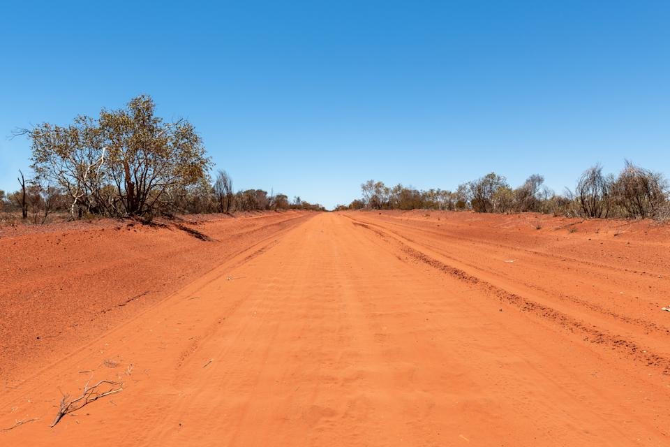 A dirt road in the red centre of the Australian outback in the Northern Territory.