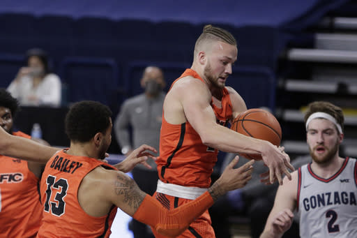 Pacific guard Broc Finstuen, center, goes after a rebound next to teammate Jeremiah Bailey, left, during the first half of the team's NCAA college basketball game against Gonzaga in Spokane, Wash., Saturday, Jan. 23, 2021. (AP Photo/Young Kwak)