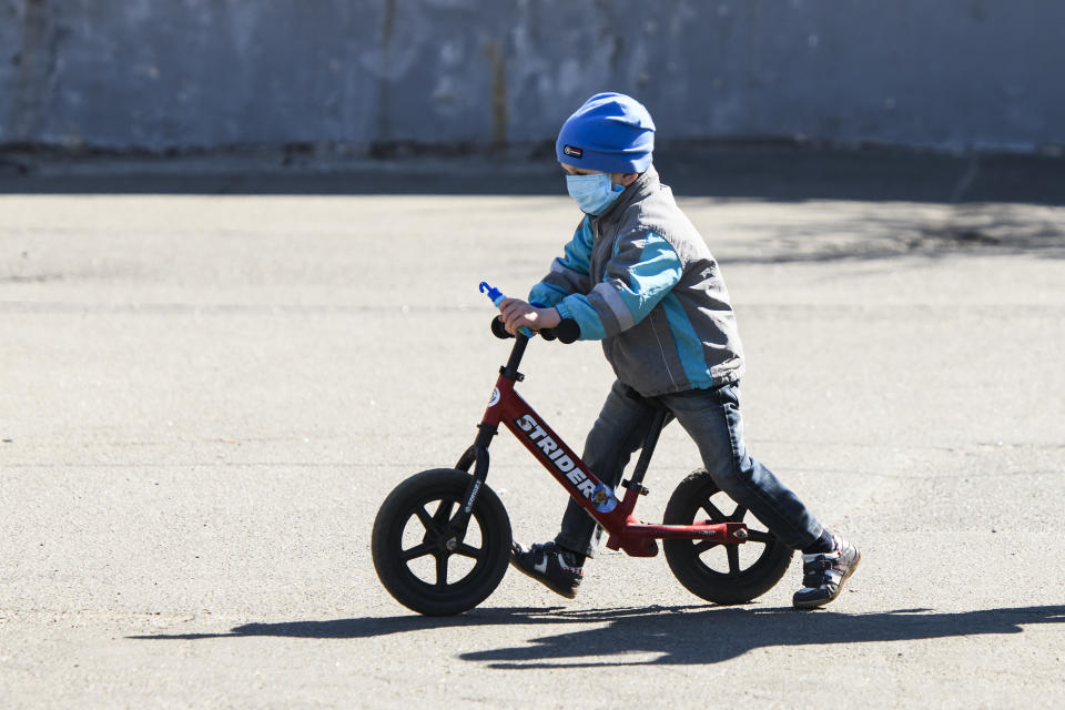 Boy in protective mask as a preventive measure against the coronavirus COVID-19 on a bicycle on street in Kyiv, Ukraine on April 06, 2020  (Photo by Maxym Marusenko/NurPhoto via Getty Images)