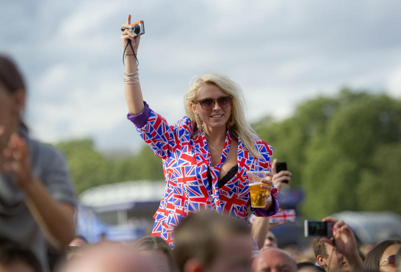 A fan wearing a British Union flag jacket, cheers the band McFly as they perform on stage for BT London Live concert in Hyde Park, central London, Saturday, Aug. 4, 2012. (AP Photo/Joel Ryan)