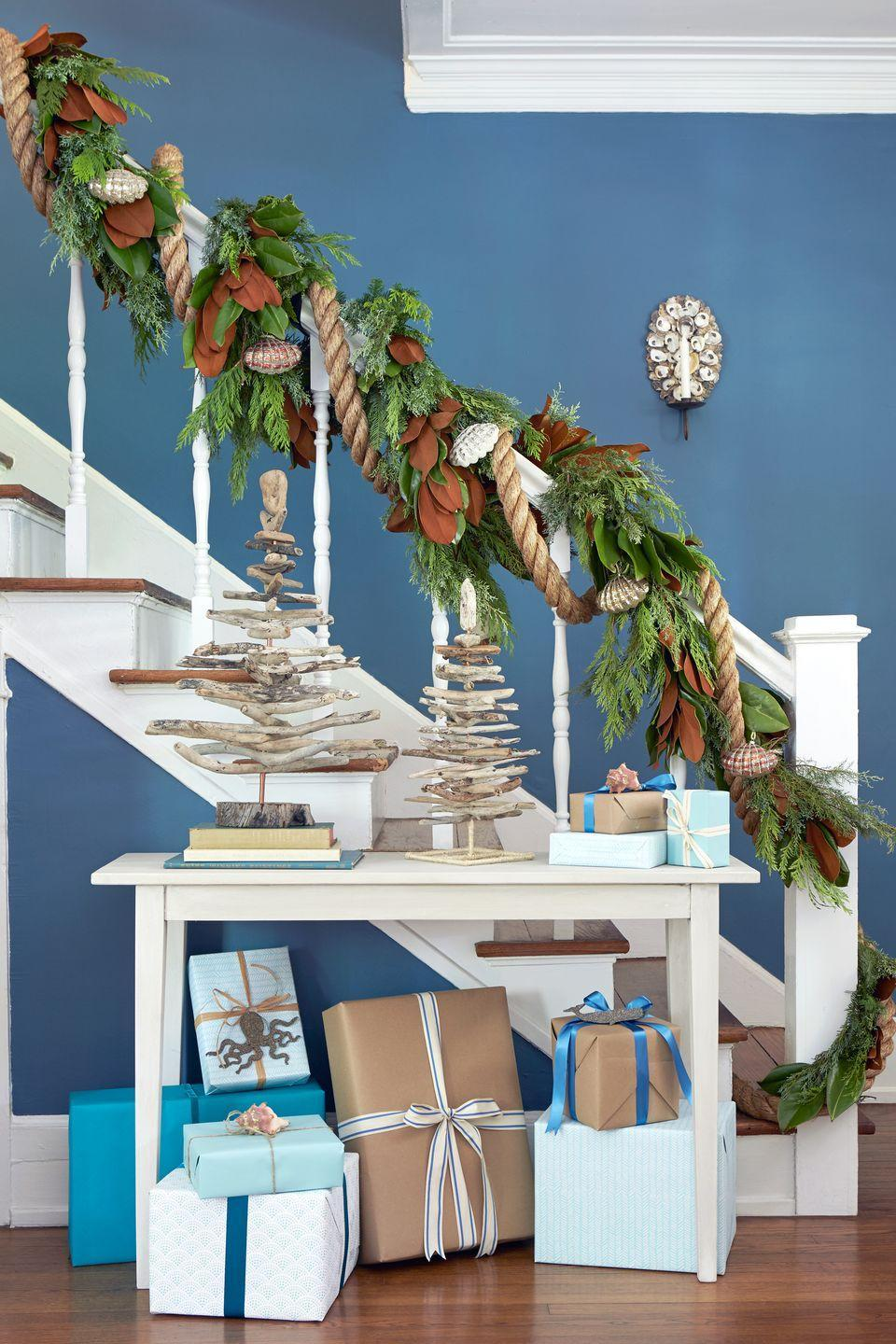 """<p>Salvaged tabletop driftwood trees, discarded shells affixed to a mirrored, candlelit sconce, and a nautical garland add festive touches to this this <a href=""""https://www.countryliving.com/home-design/decorating-ideas/g2179/country-christmas-decorating-ideas/#slide-22"""" rel=""""nofollow noopener"""" target=""""_blank"""" data-ylk=""""slk:easy-breezy stairwell"""" class=""""link rapid-noclick-resp"""">easy-breezy stairwell</a>.</p><p><a class=""""link rapid-noclick-resp"""" href=""""https://www.amazon.com/s/ref=nb_sb_noss?url=search-alias%3Dgarden&field-keywords=christmas+garland&tag=syn-yahoo-20&ascsubtag=%5Bartid%7C10050.g.1247%5Bsrc%7Cyahoo-us"""" rel=""""nofollow noopener"""" target=""""_blank"""" data-ylk=""""slk:SHOP GARLAND"""">SHOP GARLAND</a><br></p>"""