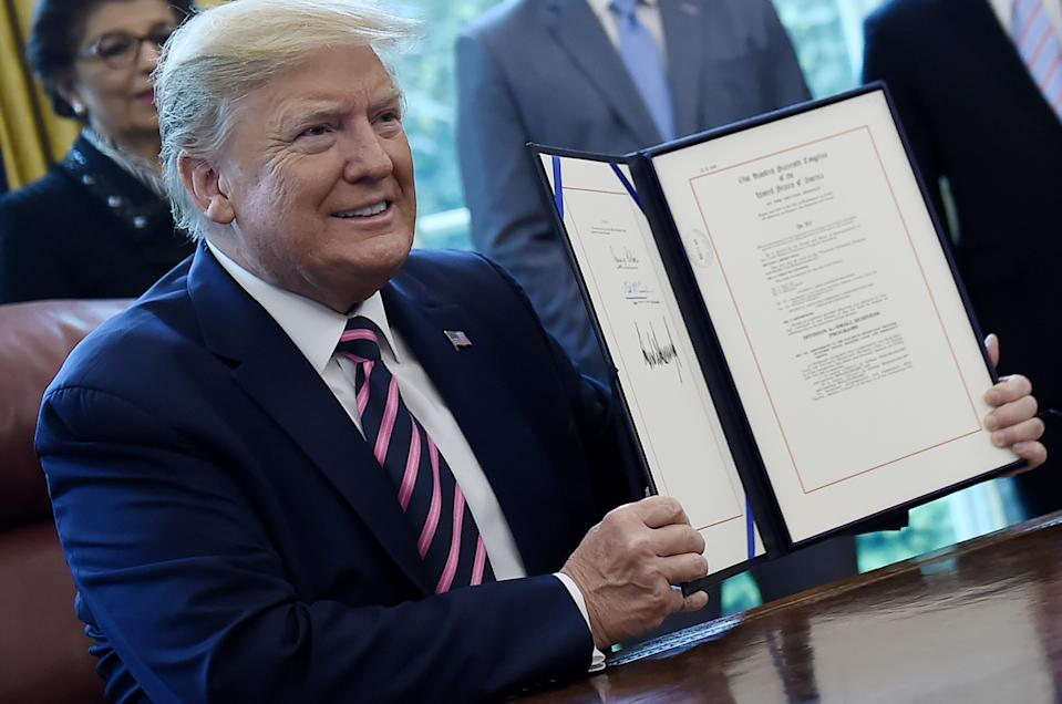 US President Donald Trump holds the signed Paycheck Protection Program and Health Care Enhancement Act in the Oval Office of the White House in Washington, DC, on April 24, 2020. - The $483 billion stimulus act will back small businesses on the brink of bankruptcy, and allocate more money for health-care providers and virus testing. (Photo by Olivier DOULIERY / AFP) (Photo by OLIVIER DOULIERY/AFP via Getty Images)