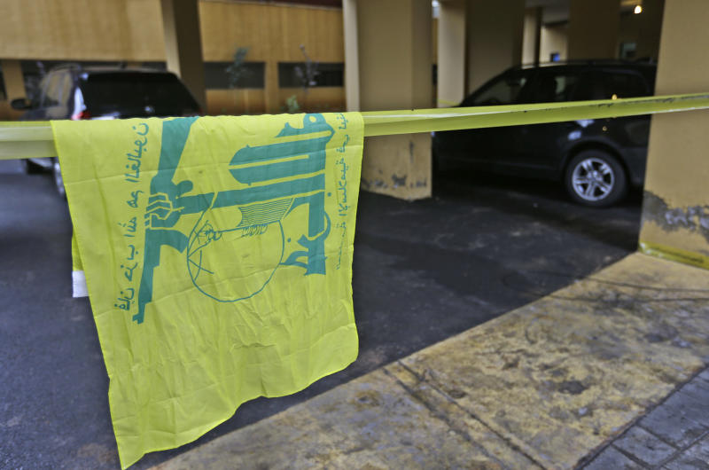 A Hezbollah flag hangs on yellow police tape sealing off the scene where Hassan al-Laqis, a senior commander for the Lebanese militant group Hezbollah, was gunned down outside his home, some two miles (three kilometers) southwest of Beirut, Lebanon, Wednesday, Dec. 4, 2013. In a statement, Hezbollah announced the death of al-Laqis and described him as one of the founding members of the group, suggesting he was a high-level commander close to the Shiite party's leadership. Hezbollah blamed Israel for the killing, something officials there quickly denied. (AP Photo/Hussein Malla)