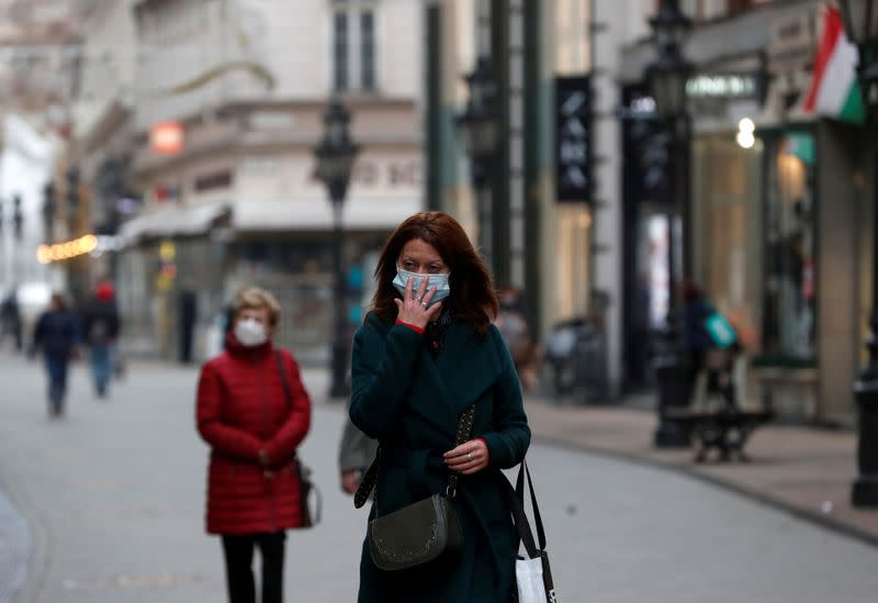 FILE PHOTO: People wearing protective face masks walk in downtown Budapest
