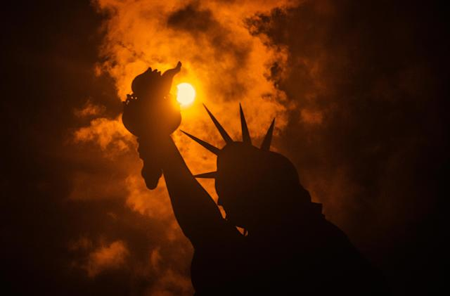 <p>The solar eclipse is seen behind the Statue of Liberty at Liberty Island in on Aug. 21, 2017 in New York City. (Photo: Noam Galai/WireImage) </p>