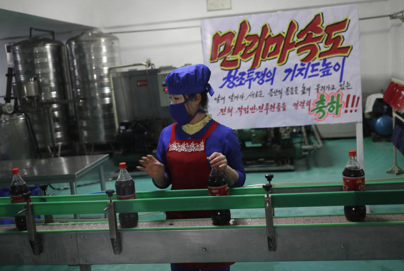 "In this March 13, 2019, photo, a worker runs a conveyor belt moving bottles of soft drinks near a propaganda banner that reads ""Let's uphold the banner of the speed of Mallima (a mythical Pegasus-type horse)"" at Kumkhop Trading Co. food factory in Pyongyang, North Korea. North Korean factories are filling city store shelves with ever better and fancier snack foods and sugary drinks, while government officials and international aid organizations warn the nation could be on the verge of a major food crisis. (AP Photo/Dita Alangkara)"