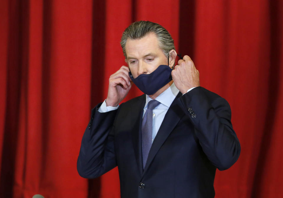 FILE - In this June 1, 2020 file photo, California Gov. Gavin Newsom takes off his face mask before news conference after meeting leaders of the African American community in Sacramento, Calif. A Chinese company paid by California to manufacturer hundreds of millions of protective masks missed a Sunday deadline for federal certification, marking the second times its shipments to the state will be delayed. (AP Photo/Rich Pedroncelli, Pool, File)