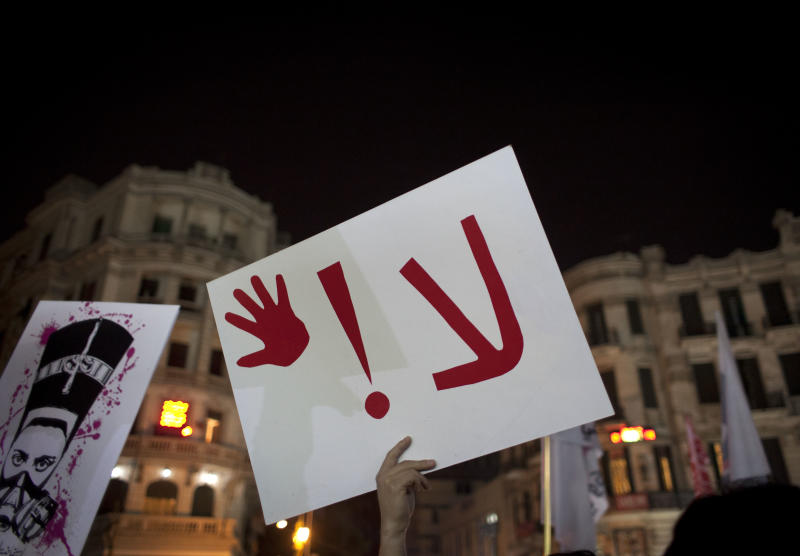 """An Egyptian woman activist holds a placard that reads """"no,"""" while taking part in a protest for women against sexual harassment and against the Islamist dominated Shura Council blaming women for the attacks against them, in Cairo, Egypt, Tuesday, Feb. 12, 2013. (AP Photo/Nasser Nasser)"""