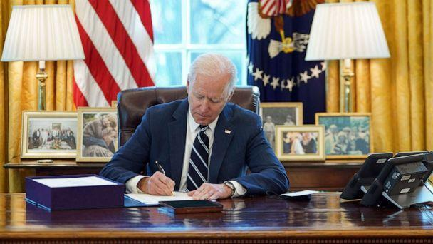 PHOTO: President Joe Biden signs the American Rescue Plan on March 11, 2021, in the Oval Office of the White House in Washington, D.C.   (Mandel Ngan/AFP via Getty Images)