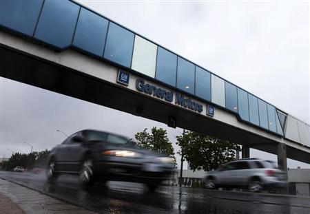 Cars pass under an overpass at the General Motors Car assembly plant in Oshawa