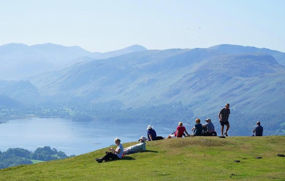 Walkers take in the view of Derwent Water in Cumbria (PA) (PA Wire)