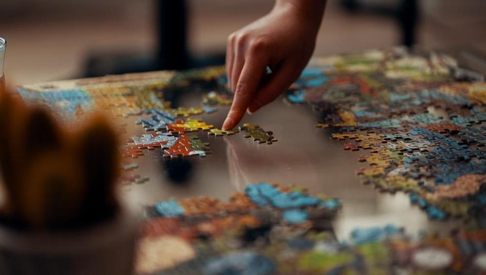 A person putting a jigsaw puzzle together. Photo: Ross Snedon