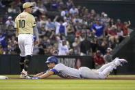 Los Angeles Dodgers shortstop Corey Seager dives into third base in front of Arizona Diamondbacks third baseman Josh Rojas (10)after hitting a triple in the seventh inning during a baseball game, Friday, Sept. 24, 2021, in Phoenix. (AP Photo/Rick Scuteri)