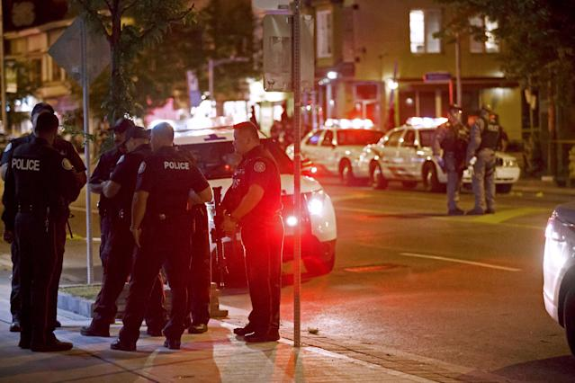 <p>Toronto Police officers walk the scene at Danforth St. at the scene of a shooting in Toronto, Ontario, Canada on July 23, 2018. (Photo: Cole Burston/AFP) </p>