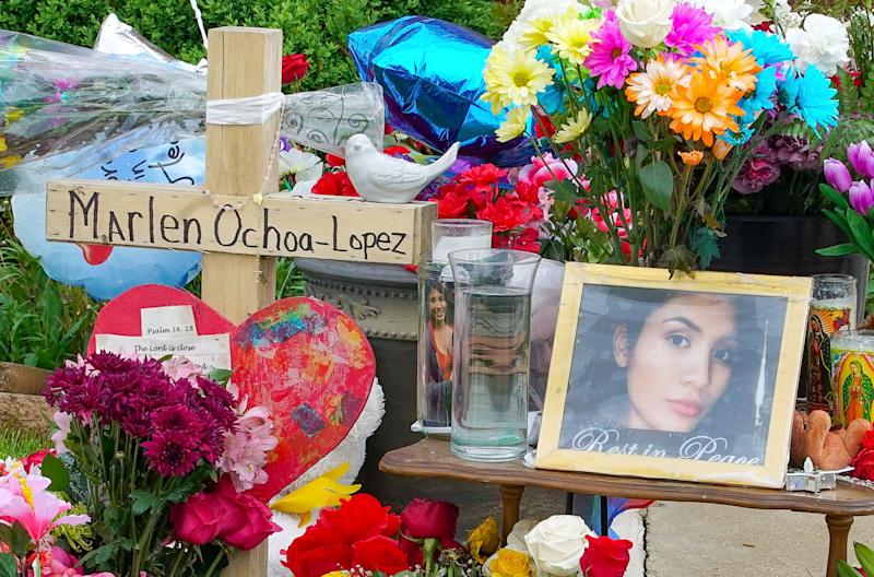 A memorial of flowers, balloons, a cross and photo of victim Marlen Ochoa-Lopez, are displayed on the lawn, Friday, May 17, 2019 in Chicago, outside the home where Ochoa-Lopez was murdered last month. Assistant State's Attorney James Murphy says a pregnant Ochoa-Lopez, who was killed and whose baby was cut from her womb, was strangled while being shown a photo album of the late son and brother of her attackers. (AP Photo/Teresa Crawford) ORG XMIT: RPTC104