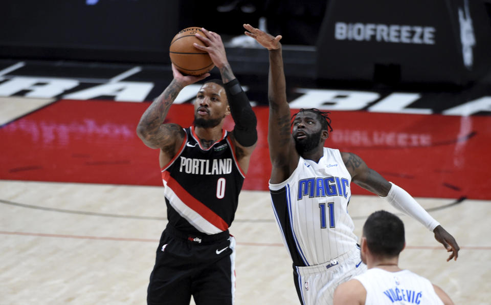 Damian Lillard with the ball in his hands shooting a 3-pointer as James Ennis stretches out his arm in an attempt to block the shot.