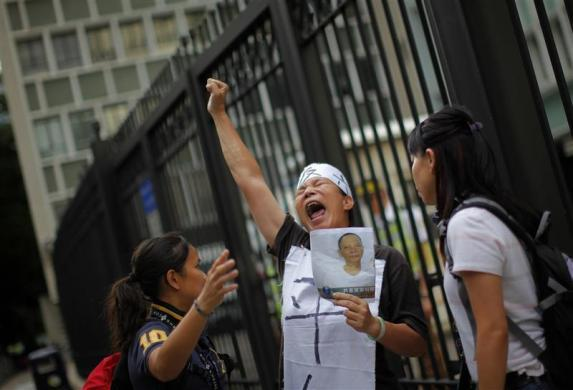 A woman holds a portrait of Chinese dissident Li Wangyang as she protests in front of the Central Government Offices in Hong Kong June 29, 2012, two days before the 15th anniversary of the territory's handover to China.