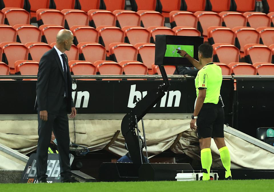 VALENCIA, SPAIN - NOVEMBER 08: Referee Jesus Gil Manzano looks at the VAR monitor during the La Liga Santander match between Valencia CF and Real Madrid at Estadio Mestalla on November 08, 2020 in Valencia, Spain. Sporting stadiums around Spain remain under strict restrictions due to the Coronavirus Pandemic as Government social distancing laws prohibit fans inside venues resulting in games being played behind closed doors. (Photo by Angel Martinez/Getty Images)