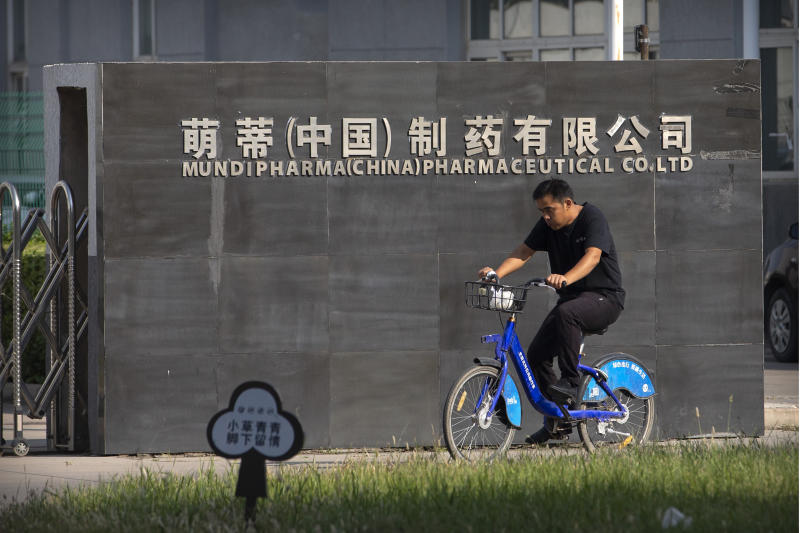 A man rides a bicycle past the entrance gate of a Mundipharma facility in an industrial park on the outskirts of Beijing, China on Sept. 27, 2019. As the Sackler's U.S. empire collapses, Mundipharma, which is also owned by the family, is using the same tactics to sell opioids in China. (AP Photo/Mark Schiefelbein)