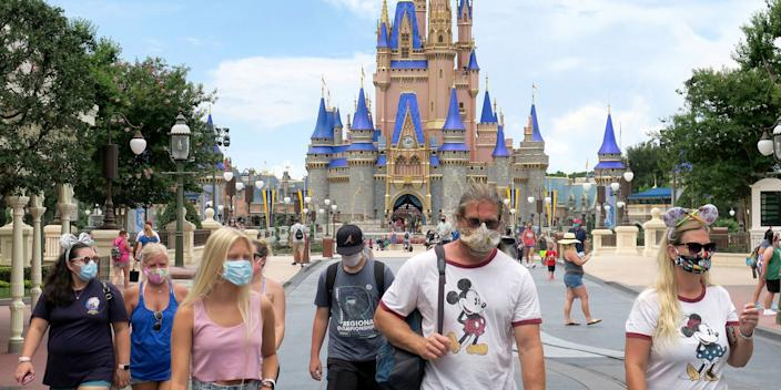 Disney World guests wear masks in front of the park's iconic castle on the first day of re-opening following a nearly four-month shutdown due to the coronavirus. Florida continues to be one of the worst-hit sates by the