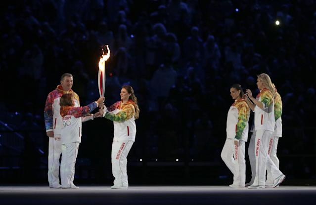 Irina Rodnina, left, receives the torch from Alina Kabaeva as Vladislav Tretyak looks at them, during the opening ceremony of the 2014 Winter Olympics in Sochi, Russia, Friday, Feb. 7, 2014