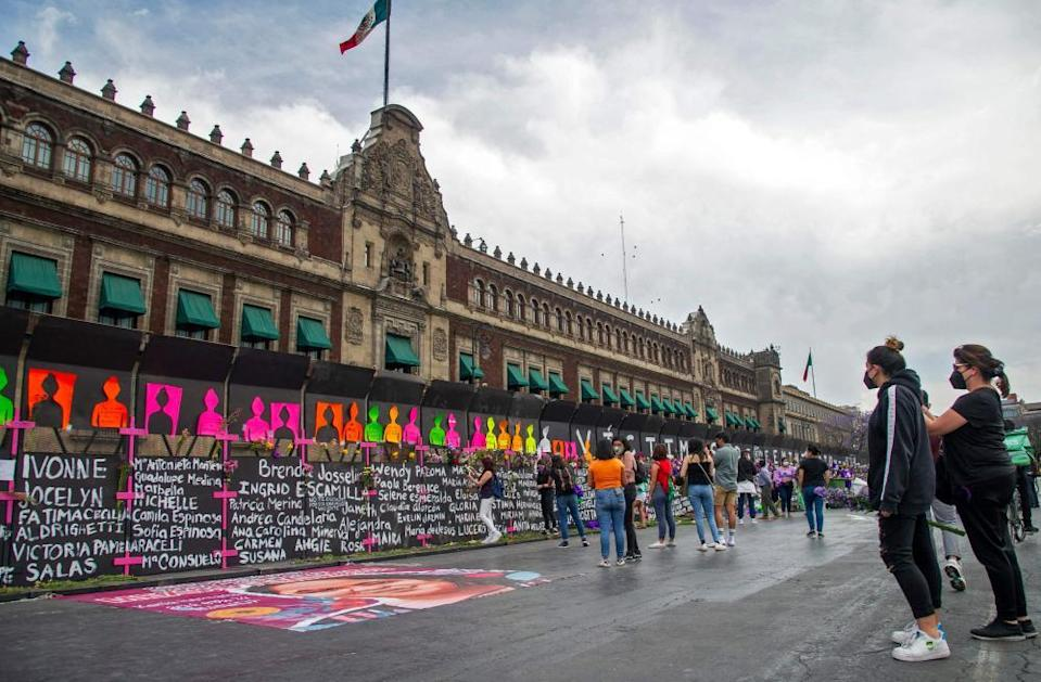 Women look at the barriers covered with the names of femicide victims surrounding the national palace.