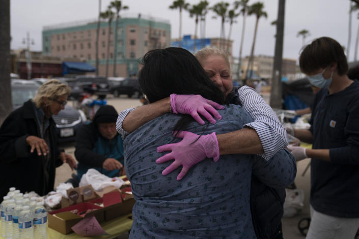 Pamela Connoly, facing camera, CEO and founder of Hope for the Hearts of the Homeless, hugs Melissa Acedera of Polo's Pantry while serving meals to homeless people in the Venice neighborhood of Los Angeles, Tuesday, June 29, 2021. (AP Photo/Jae C. Hong)