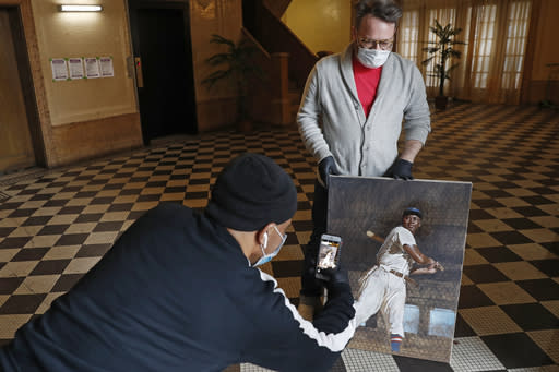 In this Wednesday, April 29, 2020, photo, delivery man Pablo Alfaro, left, takes a cell phone photograph of baseball artist Graig Kreindler's portrait of Josh Gibson while making a drop-off, as Kreindler holds his painting during a photos session in the lobby of his residence in the Brooklyn borough of New York. (AP Photo/Kathy Willens)