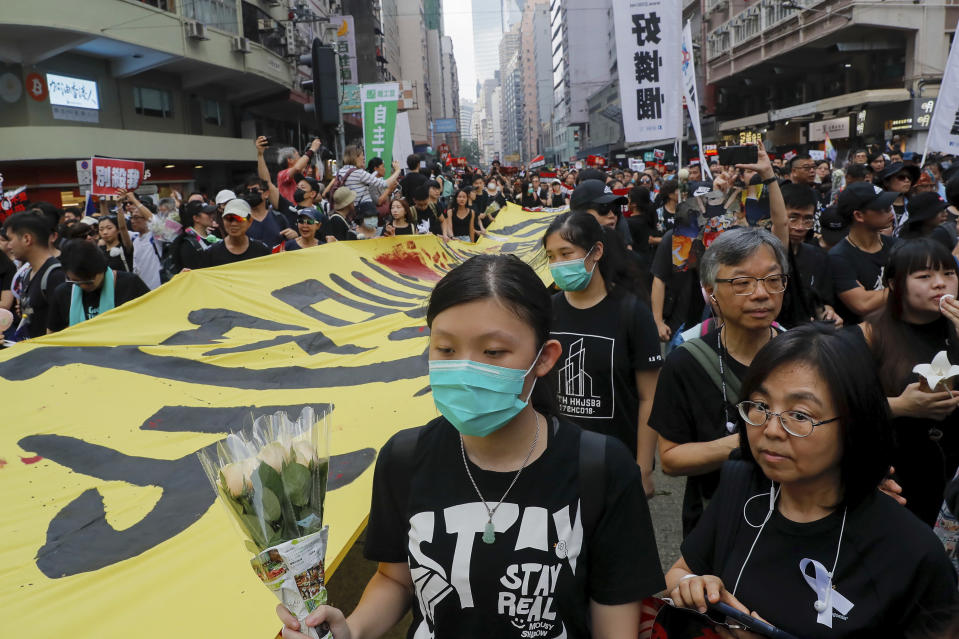Tens of thousands of protesters carry posters and banners march through the streets as they continue to protest an extradition bill, Sunday, June 16, 2019, in Hong Kong. Hong Kong residents Sunday continued their massive protest over an unpopular extradition bill that has highlighted the territory's apprehension about relations with mainland China, a week after the crisis brought as many as 1 million into the streets. (AP Photo/Kin Cheung)