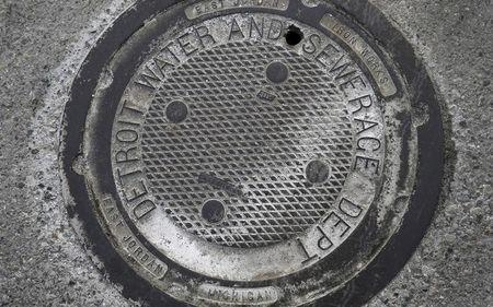 A City of Detroit Water and Sewerage man-hole cover is seen along Jefferson Avenue in the Delray neighborhood of Detroit