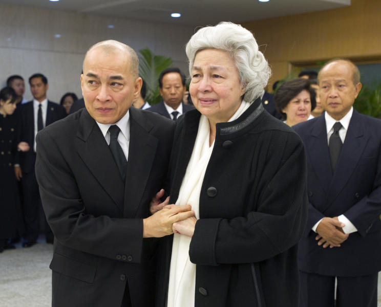 In this photo released by China's Xinhua News Agency, Cambodian Queen Mother Norodom Monineath Sihanouk and Cambodian King Norodom Sihamoni, front left, visit China's Beijing Hospital in Beijing, China to bring home the body of Cambodian former King Norodom Sihanouk, unseen, on Wednesday, Oct. 17, 2012. Sihanouk died Monday at age 89 of a heart attack in Beijing, where he had been receiving medical treatment since January for multiple ailments. His body will be flown back to Phnom Penh Wednesday. (AP Photo/Xinhua, Li Xueren) NO SALES
