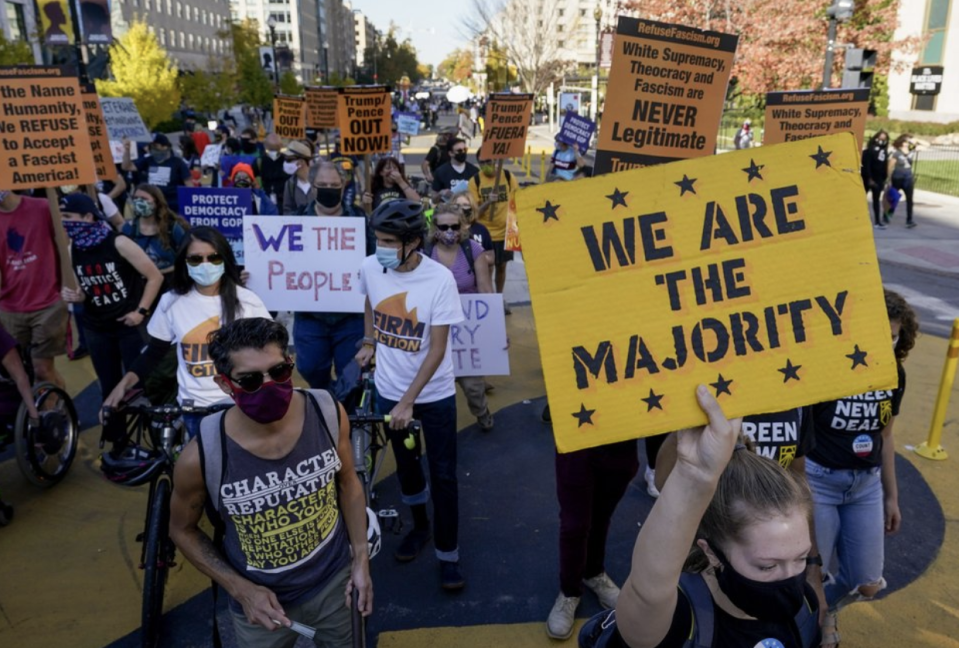 Demonstrators march through Black Lives Matter Plaza as they participate in a Count Every Vote rally on Friday in Washington. Source: AP