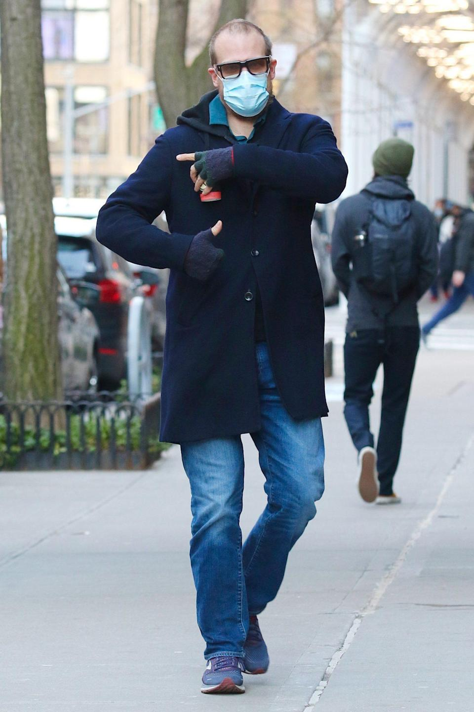 <p>David Harbour points to his shoulder where he got his vaccine shot after leaving N.Y.C.'s Javits Center on Wednesday.</p>