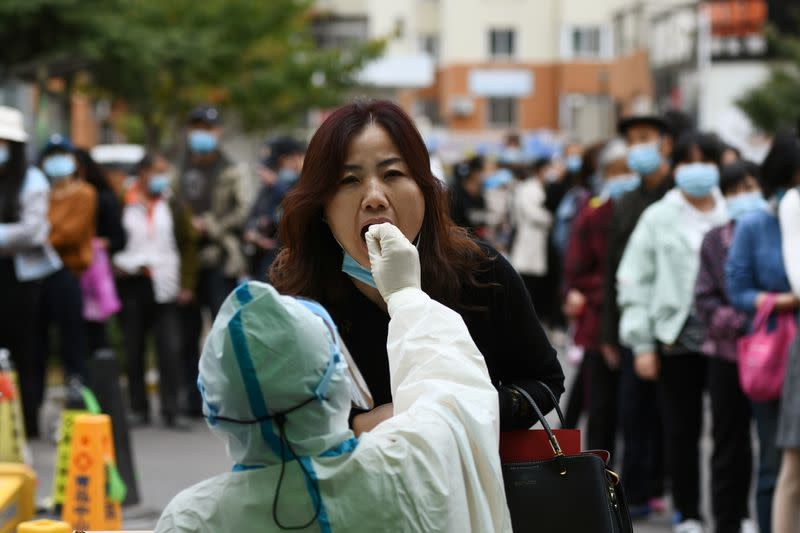 Medical worker collects a swab from a woman for nucleic acid testing, in Qingdao