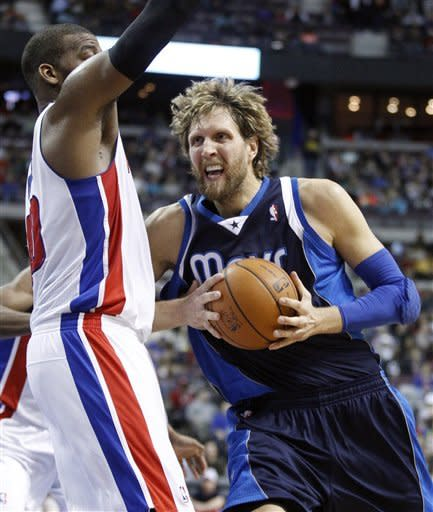 Dallas Mavericks forward Dirk Nowitzki, right, goes to the basket against Detroit Pistons center Greg Monroe, left, during the first half of an NBA basketball game Friday, March 8, 2013, in Auburn Hills, Mich. (AP Photo/Duane Burleson)