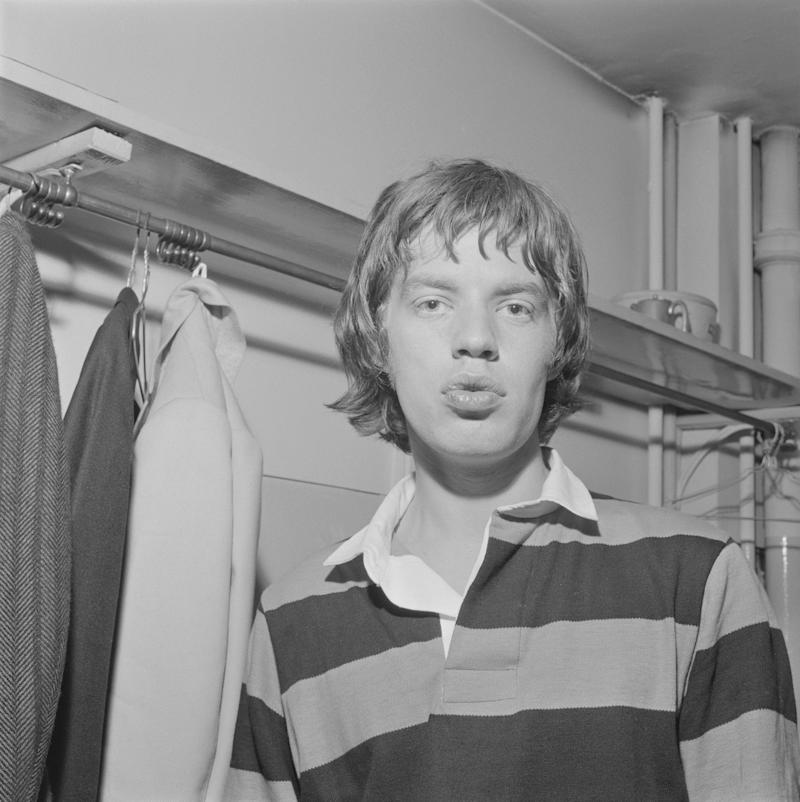 UNITED KINGDOM - 1st JANUARY: Mick Jagger from The Rolling Stones posed wearing a rugby jersey backstage on tour in Scotland in early 1964. (Photo by Mark and Colleen Hayward/Redferns)