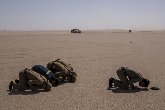 In this Sunday, Jan. 12, 2020 photo, Saudi Arabia security forces pray while a care races during stage seven of the Dakar Rally between Riyadh and Wadi Al Dawasir, Saudi Arabia. Formerly known as the Paris-Dakar Rally, the race was created by Thierry Sabine after he got lost in the Libyan desert in 1977. Until 2008, the rallies raced across Africa, but threats in Mauritania led organizers to cancel that year's event and move it to South America. It has now shifted to Saudi Arabia. The race started on Jan. 5 with 560 drivers and co-drivers, some on motorbikes, others in cars or in trucks. Only 41 are taking part in the Original category. (AP Photo/Bernat Armangue)
