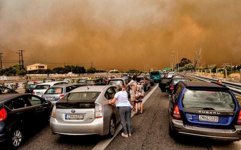 Cars are blocked at the closed National Road during a wildfire in Kineta - Credit: AFP