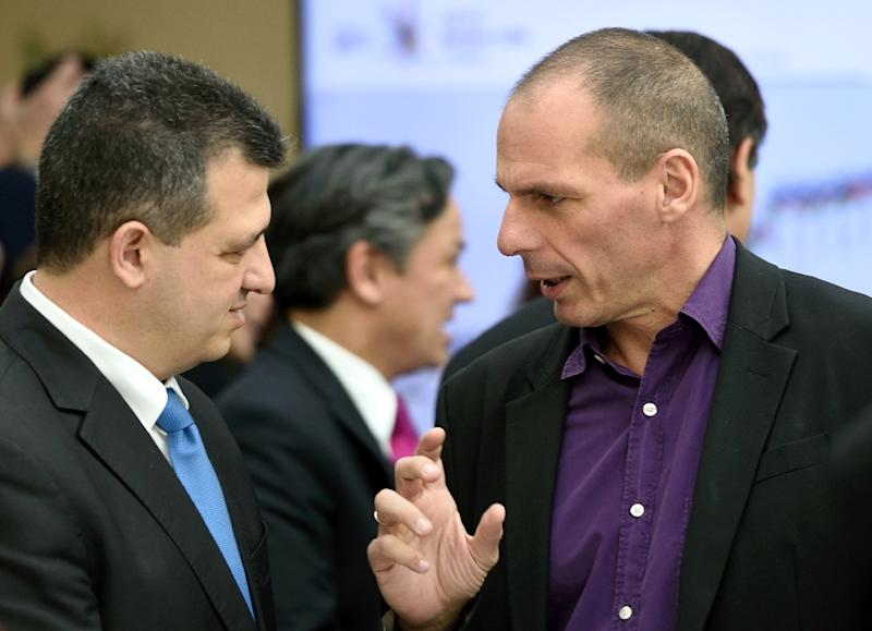 Greek Finance minister Yanis Varoufakis (R) seen prior to leaving the OECD headquarters after a visit by Greece's Prime Minister in Paris, on March 12, 2015 (AFP Photo/Eric Feferberg)