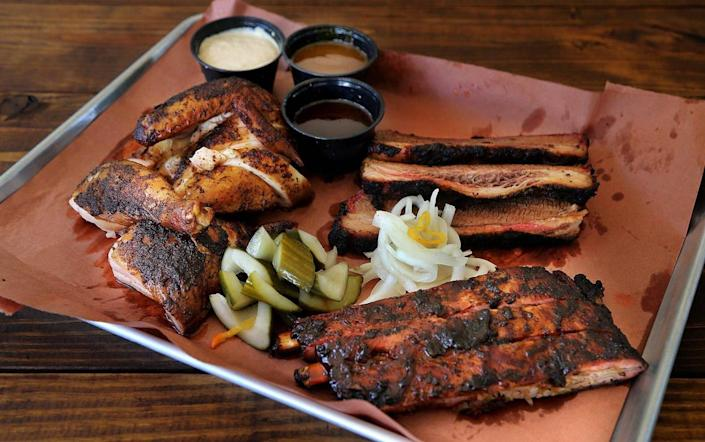 A display of delicious barbecue meats, including homemade sauces, spice rubbed chicken, spare ribs with a jerk rub, from The Drinking Pig.