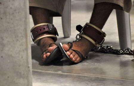 """In this photo, reviewed by a U.S. Department of Defense official, a Guantanamo detainee's feet are shackled to the floor as he attends a """"Life Skills"""" class inside the Camp 6 high-security detention facility at Guantanamo Bay U.S. Naval Base in this file pool photo taken April 27, 2010. REUTERS/Michelle Shephard/Pool"""