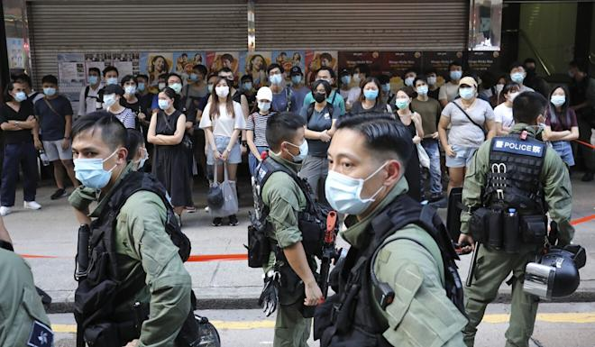 Police officers conduct stop-and-search operations on Nathan Road in Yau Ma Tei on Sunday. Photo: May Tse