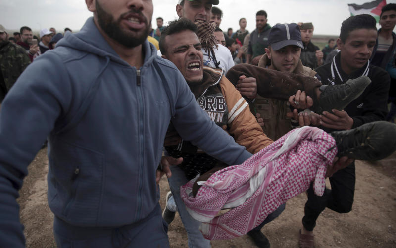 FILE - In this Friday, March 30, 2018 file photo, Palestinian protesters carry a wounded man that was shot by Israeli troops during a demonstration at the Gaza's border with Israel. The flareup of deadly violence in Gaza is of a new kind, even in the inventive annals of Mideast conflicts: Israeli soldiers shooting at Palestinian demonstrators burning tires and hurling firebombs across what looks like an international border, inflicting casualties while claiming concerns of a mass breach of the barrier. (AP Photo/Khalil Hamra, File)