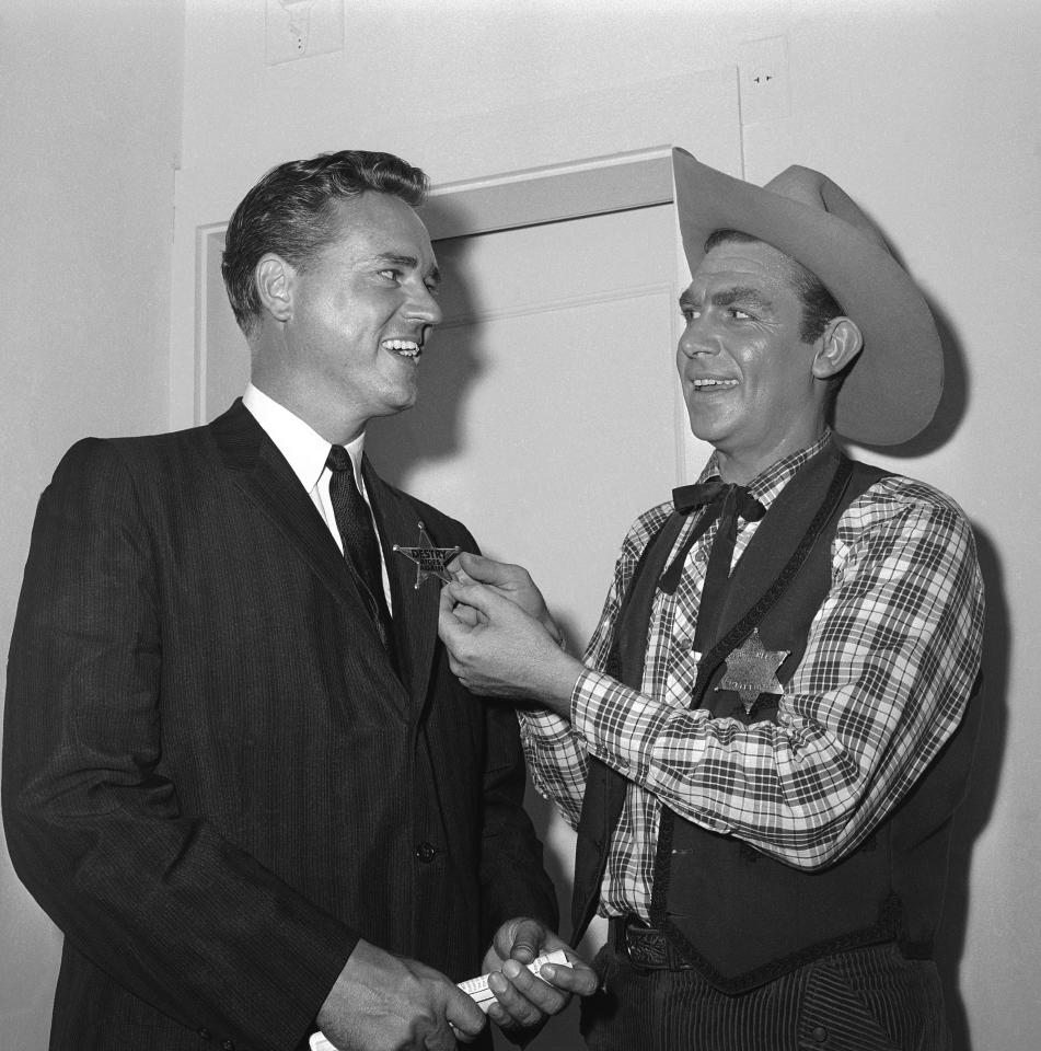 Andy Griffith, right, star of the Broadway musical 'Destry Rides Again' and a native of North Carolina, pins a badge on the lapel of Ernest F. Hollings, governor of South Carolina, after performance at night on May 21, 1959 in the Imperial Theater, New York. (AP Photo)