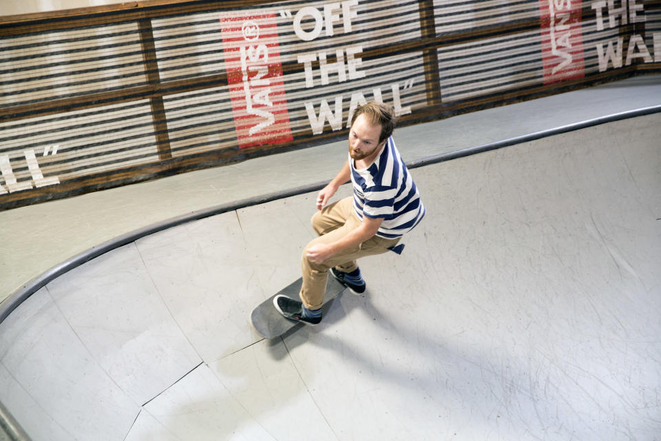 Skateboarder on a ramp. Vans signs are in the background.