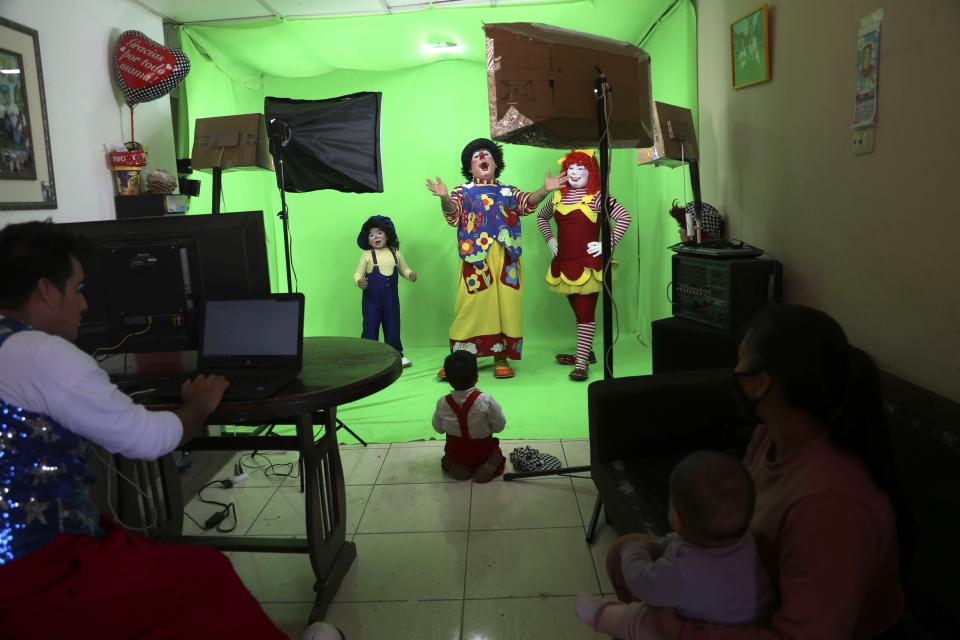 """Circus clown Carlos Olazabal, 65, whose clown name is """"Chiquitin,"""" or Little One, center, performs with his family in a studio they set up in their home on the outskirts of Lima, Peru, Monday, Aug. 10, 2020. The Olazabal family started selling live, online performances for about $3 per viewer after the COVID-19 lockdown put an end to their live circus performances. (AP Photo/Martin Mejia)"""