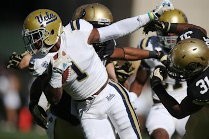 UCLA punt returner Ishmael Adams, left, breaks away for short gain from Colorado special teams player Kenneth Olugdobe in the first quarter of an NCAA football game in Boulder, Colo., on Saturday, Oct. 25, 2014. (AP Photo/David Zalubowski)