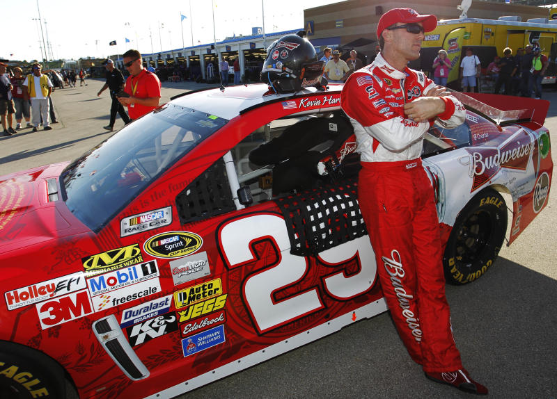 Kevin Harvick stands next to his race car after qualifying for Sunday's NASCAR Sprint Cup series auto race at Kansas Speedway in Kansas City, Kan., Friday, Oct. 4, 2013. Harvick won the pole. (AP Photo/Colin E. Braley)